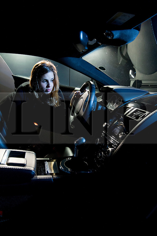 © Licensed to London News Pictures. 28/09/2012. LONDON, UK. A member of Christie's staff looks at the inside of an Aston Martin DBS used in the Bond film  'Quantum of Solace' (2008) (est. £1000,000-150,000) at the press view for the 50 Years of James Bond Auction in London today (28/09/12).  The auction, taking place on in two parts, an online sale on the 28th of September and an evening event on the 5th of October - Global James Bond Day -  is being held in aid of various charities and features props and costumes from 50 years of James Bond movies. Photo credit: Matt Cetti-Roberts/LNP