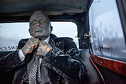 """Prof. Vladimír Franz correcting his tie in the """"Air Franz One"""" - his official campaign car - on the way from the Prague National Opera to a discussion with all Czech presidential candidates at the National Technical Library in Prague Dejvice. Franz is a prominent Czech composer and painter, stage music author and also a registered candidate in the 2013 Czech presidential election."""