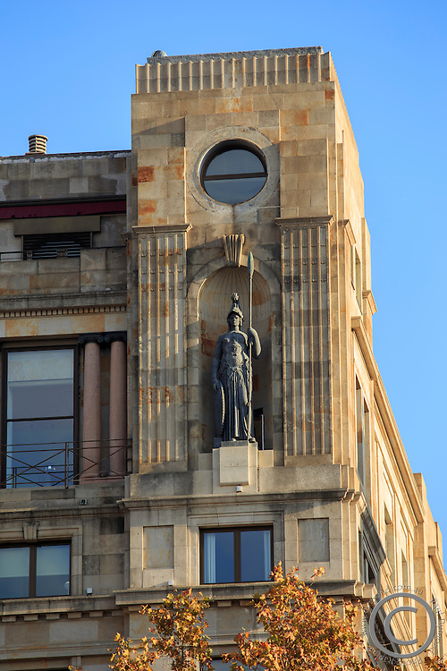 A statue high up on a building in the Placa de Catalunya in Barcelona, Spain