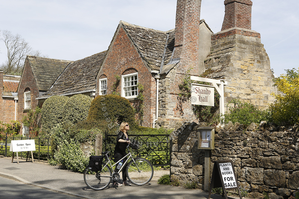 A tourist is approaching the entrance of Shandy Hall, in Coxwold, Yorkshire, England, United Kingdom.