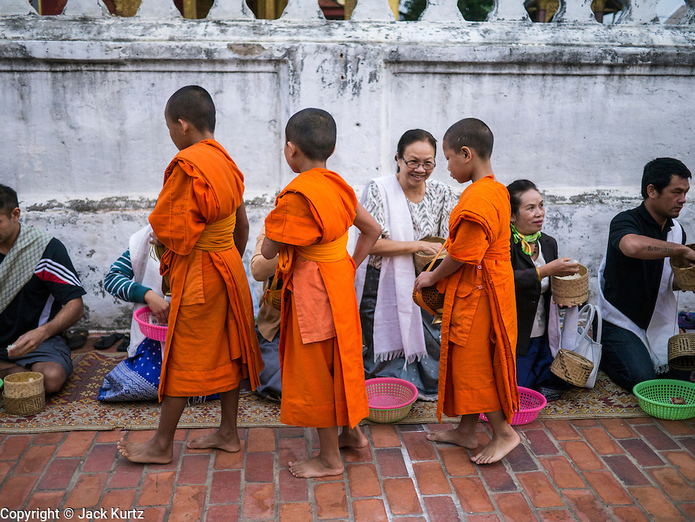 "11 MARCH 2013 - LUANG PRABANG, LAOS: Buddhist novice monks collect food during the tak bat. The ""Tak Bat"" is a daily ritual in most of Laos (and other Theravada Buddhist countries like Thailand and Cambodia). Monks leave their temples at dawn and walk silently through the streets and people put rice and other foodstuffs into their alms bowls. Luang Prabang, in northern Laos, is particularly well known for the morning ""tak bat"" because of the large number temples and monks in the city. Most mornings hundreds of monks go out to collect alms from people.    PHOTO BY JACK KURTZ"