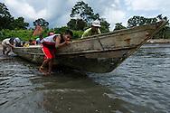 Pescadores artesanales empujando al agua a un bote con la llegada de la marea. <br /> Pueblo de Taimati en la costa del  golfo de San Miguel, Provincia de Darien,  Oc&eacute;ano Pac&iacute;fico de Panam&aacute;.   El golfo de San Miguel es el estuario m&aacute;s grande de Panam&aacute;, con una extensi&oacute;n de unos 1,760 km2.  La comunidad de Taimati  esta conformada por ind&iacute;genas Embera-Wounaan y criollos dedicados principalmente a la pesca artesanal y cultivos como el arroz, yuca y pl&aacute;tanos.