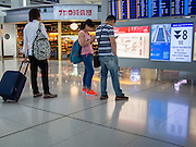 14 AUGUST 2013 - HONG KONG:  Passengers check a flight status board that is showing Typhoon Warning 8, the highest, most severe level, at Hong Kong International Airport. Dozens of flights were delayed at one of the busiest airports in Asia and Hong Kong raised their alert to level 8, the highest, and closed schools and many businesses because of Severe Typhoon Utor. The storm passed within 260 kilometers of Hong Kong before making landfall in mainland China. Severe Typhoon Utor (known in the Philippines as Typhoon Labuyo) is an active tropical cyclone located over the South China Sea. The eleventh named storm and second typhoon of the 2013 typhoon season, Utor formed from a tropical depression on August 8. The depression was upgraded to Tropical Storm Utor the following day, and to typhoon intensity just a few hours afterwards. The Philippines, which bore the brunt of the storm, reported 1 dead in a mudslide and 23 fishermen missing at sea.   PHOTO BY JACK KURTZ