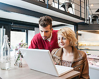 Young couple using laptop in cafe
