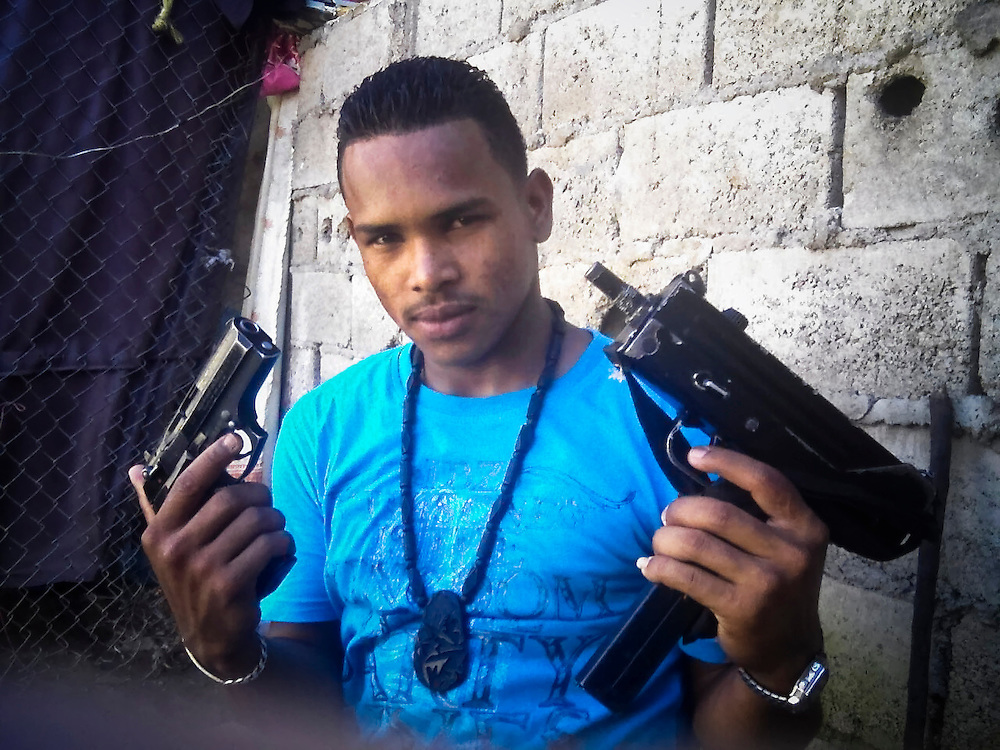 """**IMAGE PROVIDED BY A PRISONER WHO WISHES TO REMAIN ANONYMOUS, PLEASE CREDIT ACCORDINGLY**  One of Teófilo Rodríguez's bodyguards poses for a portrait with the weapons he carries inside San Antonio prison in Porlamar, Venezuela. """" There's enough guns and ammunition here to start a war,"""" said prisoner Paul Makin, 33, """"handguns, machine guns, AK-47s, AR-15s, M-16s, magnums, colts, Berettas, Uzis, Mac 10, Ingram's...You name them, it's in here."""""""