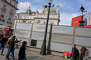 "Pedestrians point towards a London site next to a temporary construction hoarding beneath the partially hidden statue of the world famous London Victorian-era landmark, Eros in Piccadilly Circus, on 25th February 2020, in London, England. Eros, or the Shaftesbury Memorial Fountain is located at the southeastern side of Piccadilly Circus in London, United Kingdom. Moved after World War II from its original position in the centre, it was erected in 1892–1893 to commemorate the philanthropic works of Lord Shaftesbury, who was a famous Victorian politician and philanthropist. The monument is surmounted by Alfred Gilbert's winged nude statue generally, though mistakenly, known as Eros. This has been called ""London's most famous work of sculpture."""