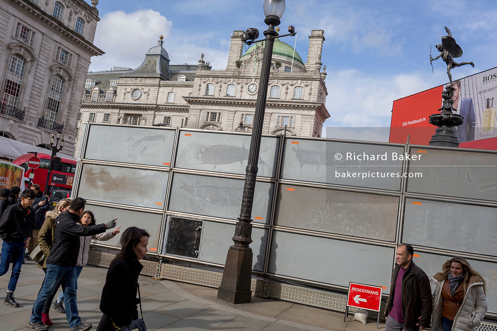 """Pedestrians point towards a London site next to a temporary construction hoarding beneath the partially hidden statue of the world famous London Victorian-era landmark, Eros in Piccadilly Circus, on 25th February 2020, in London, England. Eros, or the Shaftesbury Memorial Fountain is located at the southeastern side of Piccadilly Circus in London, United Kingdom. Moved after World War II from its original position in the centre, it was erected in 1892–1893 to commemorate the philanthropic works of Lord Shaftesbury, who was a famous Victorian politician and philanthropist. The monument is surmounted by Alfred Gilbert's winged nude statue generally, though mistakenly, known as Eros. This has been called """"London's most famous work of sculpture."""""""