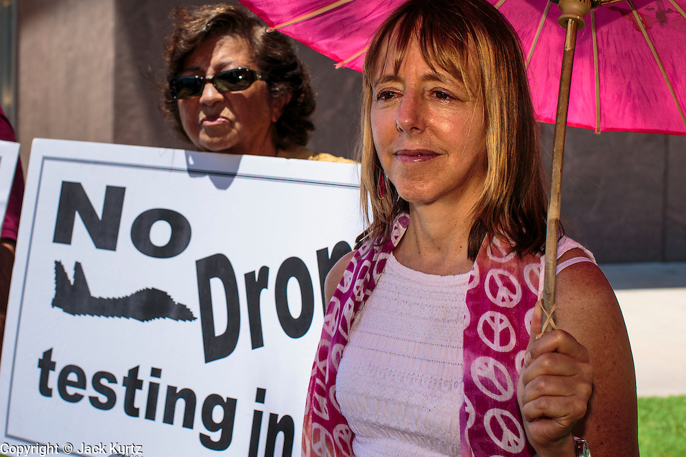 "31 JULY 2012 - PHOENIX, AZ: MEDEA BENJAMIN, right, waits to speak at a press conference at the Arizona State Capitol Tuesday. Medea is a political activist, best known for co-founding Code Pink and, along with her husband, activist and author Kevin Danaher, the fair trade advocacy group Global Exchange. She was also a Green Party candidate in 2000 for the United States Senate. She appeared in Phoenix to promote her new book, ""Drone Warfare: Killing by Remote Control."" She, and other members of Code Pink, presented a letter to Arizona Gov. Jan Brewer protesting Brewer's request to use the state's airspace to train drone pilots.   PHOTO BY JACK KURTZ"
