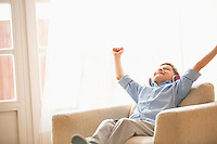Happy boy with arms raised enjoying music while relaxing on armchair at home
