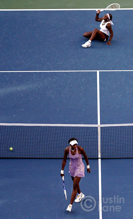Venus Williams (bottom) walks away from the net after winning a point against her sister Serena in the second set of Venus' straight set victory over her sister during the fourth round of the 2005 US Open Tennis Tournament.