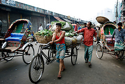 BANGLADESH DHAKA KAWRAN BAZAAR 3MARB05 - A van puller devours an apple while on the move at Kawran Bazaar vegetable market. The Bazaar has been in the Tejgaon area for at least 30 years and is one of the largest markets in Dhaka city...jre/Photo by Jiri Rezac..© Jiri Rezac 2005..Contact: +44 (0) 7050 110 417.Mobile:  +44 (0) 7801 337 683.Office:  +44 (0) 20 8968 9635..Email:   jiri@jirirezac.com.Web:    www.jirirezac.com..© All images Jiri Rezac 2005 - All rights reserved.