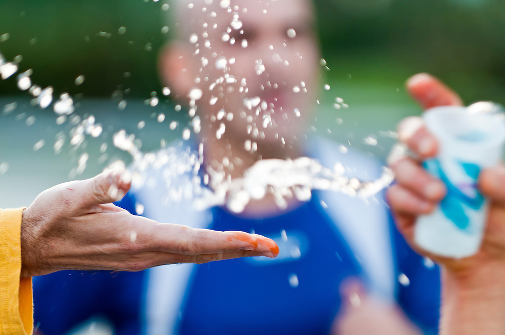 Runner grabbing water during a marathon from a volunteer hand. Use of selective focus.