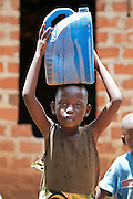 Angeo Pone, one of Nusula Ssewanonda neighbours, comes to buy water from her tank. Nusula is a member of Kirangira Womens group in Mukono District, Uganda. She recently sold a bull calf and has invested the money in drainpipes and a big water tank. She now collects rainwater from the roof of her house and sells it to people in her village. She then used this money to install bio gas.
