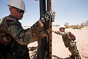 12 JUNE 2006 - SAN LUIS, AZ: Soldiers from the Utah Army National Guard install a section of fence on the US/Mexico border. Mexico is behind the soldier on the right. Fifty five members of the 116th Engineer Company, Combat Support Engineers, of the Utah Army National Guard are in San Luis, AZ, to build a fence and improve roads east of the San Luis Port of Entry on the US/Mexico border. The unit is the first of an estimated 6,000 US military personnel, almost all of them Army National Guard, who will be dispatched to the US/Mexico border by President Bush to help control immigration on the border. The Guardsmen will primarily build roads and fence and staff surveillance centers. They will not be engaged in first line law enforcement work.  Photo by Jack Kurtz