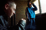 Two teenage boys one drinking a can of lager Stella Artois while the other skins up a spliff Lambeth Walk South London c.2000