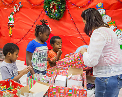 Christiane Levine hands out balloons and other gifts to Yandre Smith, Jeni-Yah Freeman, Yaadden Smith.  Children were able to choose from a variety of gifts from Santa.  The Rotary Club of St. Thomas East hosts Breakfast with Santa at Ivanna Eudora Kean High School where children and their families shared a pancake breakfast, played with gifts, and took pictures with Santa.  St. Thomas, USVI.  5 December 2015.  © Aisha-Zakiya Boyd