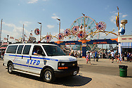 The NYPD, New York Police Department, officers in SUV vehicle patrol the boardwalk at the Fourth Annual History Day at Deno's Wonder Wheel Amusement Park and The Coney Island History Project, has family fun music, history, and entertainment at historic Coney Island.