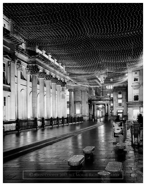 Black and white photograph of the 'Celestial Sky' winter lighting scheme at Royal Exchange Square, Glasgow. Mounted print available to purchase.