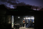 "A manager at Mr Huang's factory contacts a client to inform him the goods are ready, as dawn breaks in Zhongshan city, China..This picture is part of a photo and text story on blue jeans production in China by Justin Jin. .China, the ""factory of the world"", is now also the major producer for blue jeans. To meet production demand, thousands of workers sweat through the night scrubbing, spraying and tearing trousers to create their rugged look. .At dawn, workers bundle the garment off to another factory for packaging and shipping around the world..The workers are among the 200 million migrant labourers criss-crossing China.looking for a better life, at the same time building their country into a.mighty industrial power."