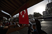 Gaziantep | 12 September 2015<br /> <br /> A shop owner attaches a turkish national flag to the sun blind in front of his shop in the center of the south-eastern turkish city of Gaziantep while a woman with a head scarf passes by.<br /> Flags are waving all over the country to commemorate the killing of over 30 police officers in the struggle between the turkish government and kurdish so-called &quot;terrorist group&quot; PKK.<br /> <br /> &copy;peter-juelich.com<br /> <br /> [No Model Release | No Property Release]