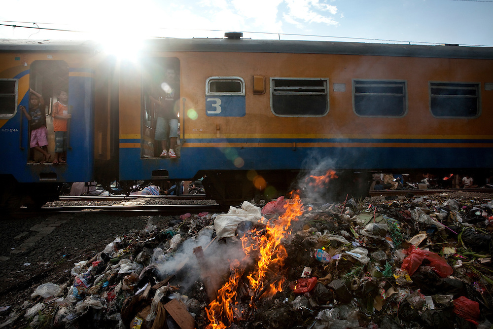 A train passes through a poor neighborhood in jakarta. Garbage is burned next to the train line, one of the few places where there is open space in the crowded neighboehood.  Jakarta, Indonesia.