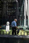 A bald-headed office worker waits next to head sculptures outside the Leadenhall Building during the 2018 heatwave in the City of London, the capital's financial district, on 24th July 2018, in London, England.