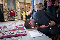 """3 June 2018, Novi Sad, Serbia: A differently abled person kneels and bows to pray during Sunday service in the Eastern Orthodox Cathedral Church of the Holy Great Martyr George. On 31 May - 6 June 2018, in Novi Sad, Serbia, the Serbian Orthodox Church stood as one of the host churches of the Conference of European Churches General Assembly. More than 400 delegates, advisors, stewards, youth, staff, and distinguished guests took part in the Assembly and related events, gathered under the theme, """"You shall be my witnesses""""."""