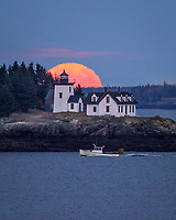 A lobster boat passes under Indian Island Lighthouse in Rockport as a full, and very orange, moon rises behind the opposite shore.