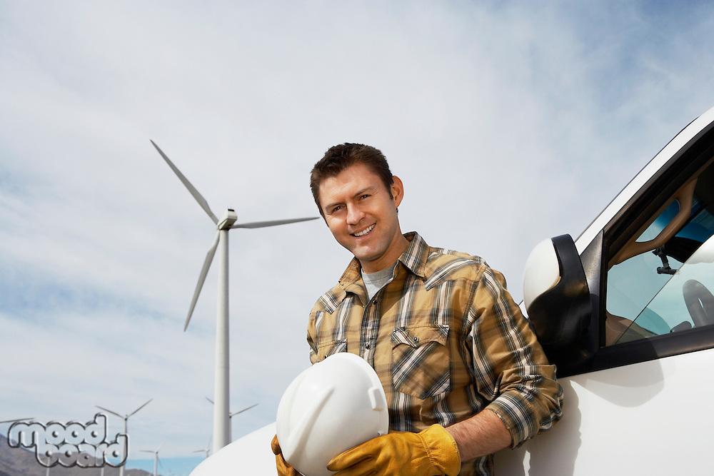 Engineer by car at wind farm, portrait