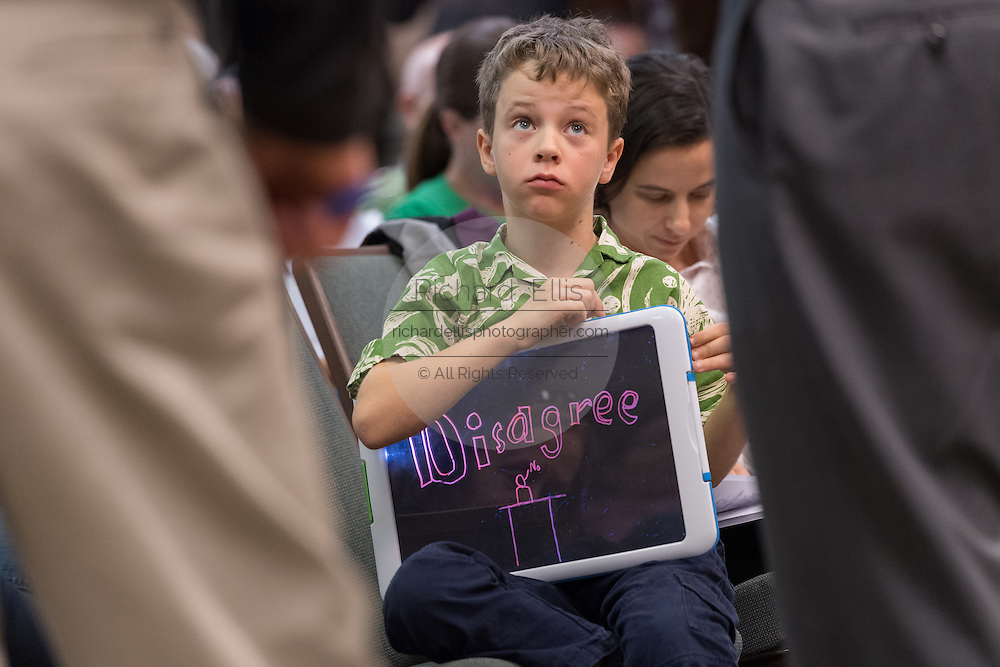 A young boy listens to the answer to his question from U.S. Sen. Tim Scott during a town hall meeting with constituents February 18, 2017 in Mount Pleasant, South Carolina. Hundreds of concerned residents turned up for the meeting to address their opposition to President Donald Trump during a vocal meeting held by U.S. Rep. Mark Sanford and Senator Tim Scott.