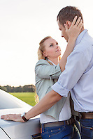 Side view of romantic young couple by car at countryside