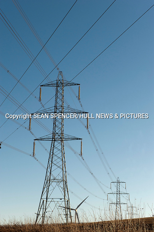 An electricity pylon in East Yorkshire, UK, with a wind turbine in the background and a telegraph pole on the left.