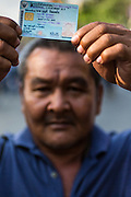 "01 FEBRUARY 2014 - BANGKOK, THAILAND:  A Thai voter holds his national ID card over his head to a march to a polling place to vote. The voters were turned back by police who blocked access to the polls because armed anti-government protestors would not allow voters to cast their ballots. Thais went to the polls in a ""snap election"" Sunday called in December after Prime Minister Yingluck Shinawatra dissolved the parliament in the face of large anti-government protests in Bangkok. The anti-government opposition, led by the People's Democratic Reform Committee (PDRC), called for a boycott of the election and threatened to disrupt voting. Many polling places in Bangkok were closed by protestors who blocked access to the polls or distribution of ballots. The result of the election are likely to be contested in the Thai Constitutional Court and may be invalidated because there won't be quorum in the Thai parliament.   PHOTO BY JACK KURTZ"