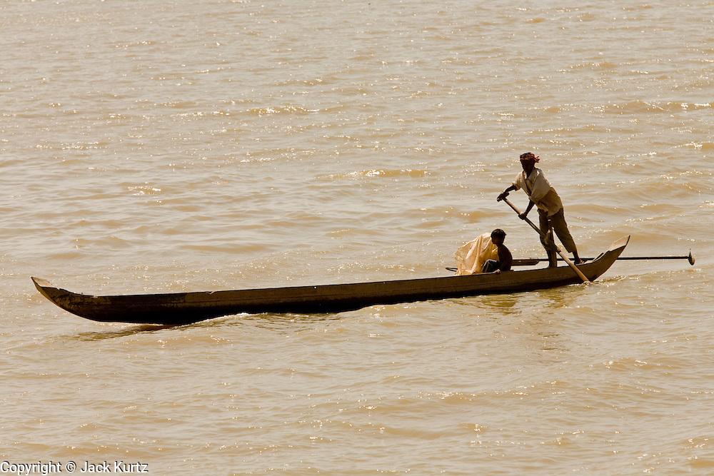 17 MARCH 2006 - KAMPONG CHHNANG, KAMPONG CHHNANG, CAMBODIA: A man and boy paddle a canoe on the Tonle Sap River in the city of Kampong Chhnang in central Cambodia. PHOTO BY JACK KURTZ