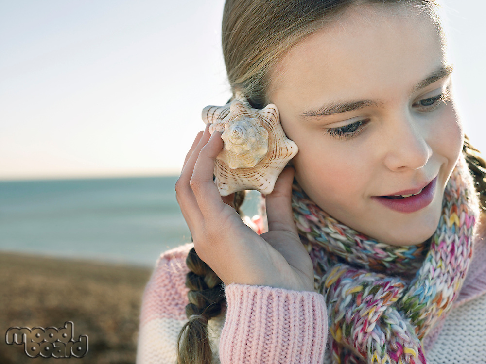 Pre teen girl listening to seashell standing on beach close up