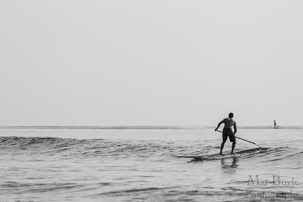 Paddleboarders rides a wave in the Atlantic Ocean in Ocean City, NJ on August 22, 2012. (photo / Mat Boyle)
