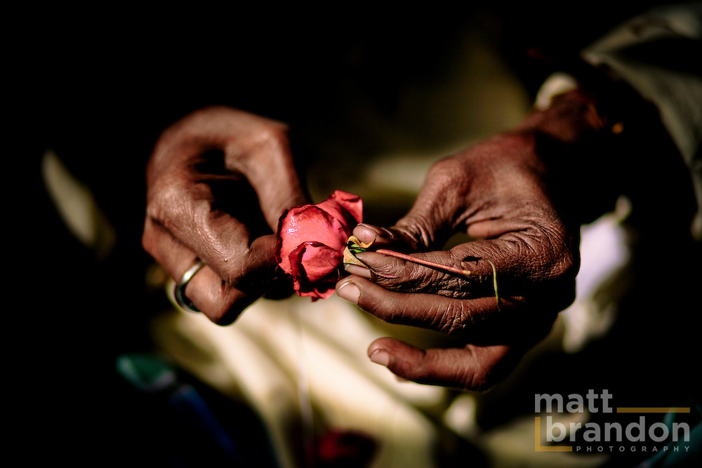 the hands of a shopkeeper string roses to make garlands for the tomb of Nizamuddin.
