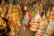 "05 JULY 2011 - BANGKOK, THAILAND:     A vendor in her Buddhist supply shop on Bamrung Muang Street in Bangkok. Thanon Bamrung Muang (Thanon is Thai for Road or Street) is Bangkok's ""Street of Many Buddhas."" Like many ancient cities, Bangkok was once a city of artisan's neighborhoods and Bamrung Muang Road, near Bangkok's present day city hall, was once the street where all the country's Buddha statues were made. Now they made in factories on the edge of Bangkok, but Bamrung Muang Road is still where the statues are sold. Once an elephant trail, it was one of the first streets paved in Bangkok, it is the largest center of Buddhist supplies in Thailand. Not just statues but also monk's robes, candles, alms bowls, and pre-configured alms baskets are for sale along both sides of the street.        PHOTO BY JACK KURTZ"