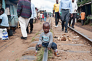 Child sitting on the railtrack in Kibera slum, Kenya