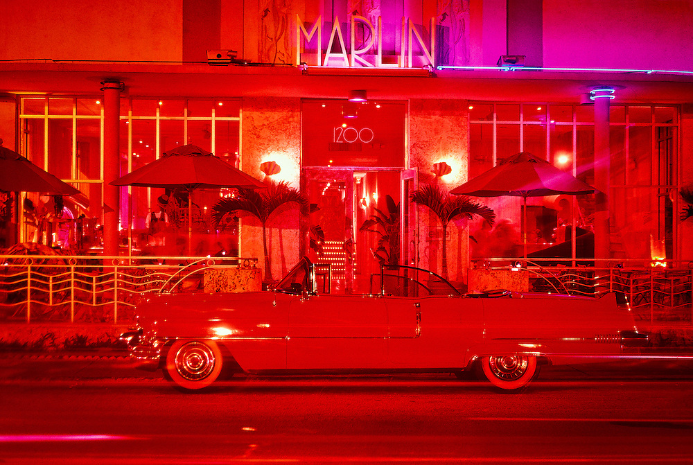 The streamlined, Marlin Hotel on Miami Beach's neon-lit Collins Avenue with a vintage, pink, 1956 Cadillac convertible parked in front. <br />