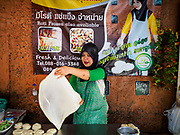01 SEPTEMBER 2017 - BANGKOK, THAILAND: A woman makes roti at the celebration of Eid al-Adha at Haroon Mosque in Bangkok. Eid al-Adha is also called the Feast of Sacrifice, the Greater Eid or Baqar-Eid. It honours the willingness of Abraham to sacrifice his son. Goats, sheep and cows are sacrificed in a ritualistic manner after services in the mosque. The meat from the sacrificed animal is supposed to be divided into three parts. The family retains one third of the share; another third is given to relatives, friends and neighbors; and the remaining third is given to the poor and needy.     PHOTO BY JACK KURTZ