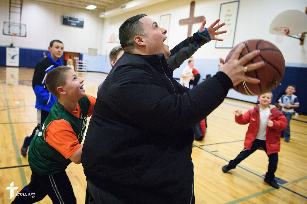 Vicar David Blas, missionary-at-large at LCMS Sheboygan County Hispanic Outreach and St. John's Lutheran Church of Plymouth, Wis., joins in a small pickup game following a scheduled game between schools on Thursday, Jan. 28, 2016, in Plymouth. LCMS Communications/Erik M. Lunsford