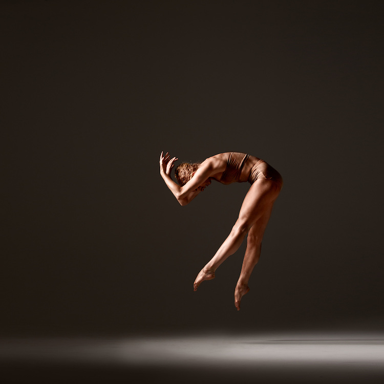 Contemporary female dancer, Andrea Wolf, jumping and painted in gold, taken in the photo studio on a dark background. Photograph taken in New York City by photographer Rachel Neville.