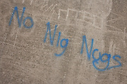 Racist references to the ethnic black race sprayed in blue aerosol on a River Thames defence wall at Grays, Essex