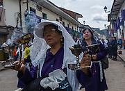 A woman holding burning incense sings a hymn in the procession of El Senor de los Milagros, Cusco, Peru.