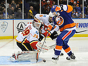 Calgary Flames goalie Reto Berra (29) and Mark Giordano (5) defend against New York Islanders' Kyle Okposo (21) during an NHL hockey game on Thursday, Feb. 6, 2014, in Uniondale, N.Y. (AP Photo/Kathy Kmonicek)