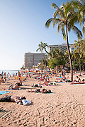 Crowds of people sunbathe on Waikiki Beach.