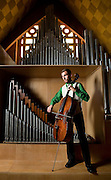 Caleb Staehr poses with his cello in front of the pipe organ at Trinity Lutheran Church in Grand Island. Staehr graduated from Heartland Lutheran in May and will pursue music education at Concordia University in Seward this fall. (Independent/Matt Dixon)