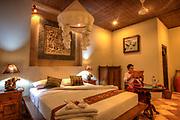 Tourist lodge bedroom, woman reading, Bali, Indonesia.