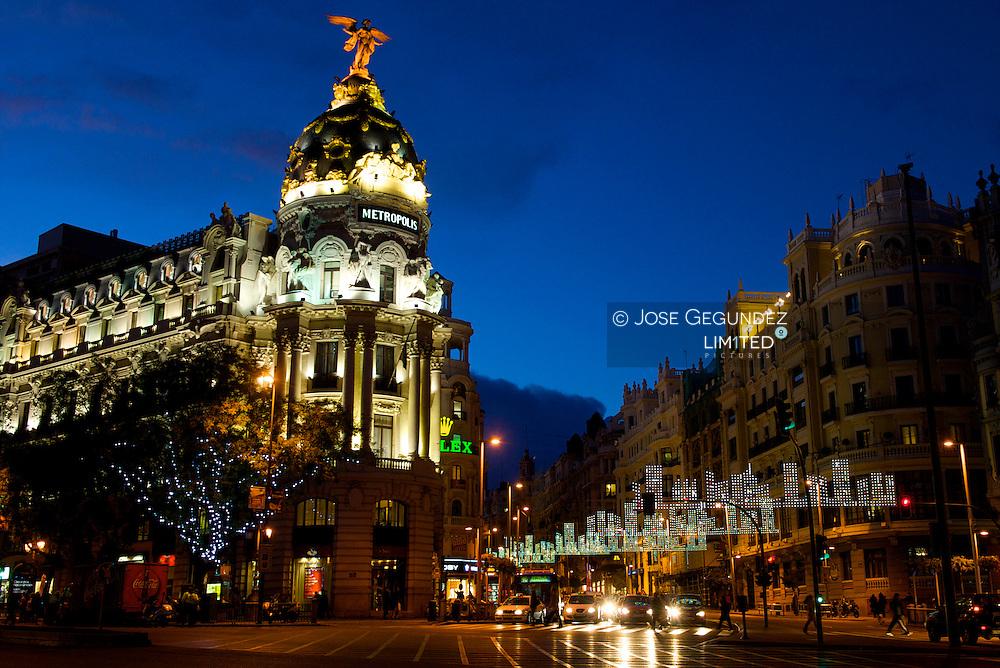 llumination of Christmas in Madrid. Metropolis Building in Alcala Street with Gran Via Street.